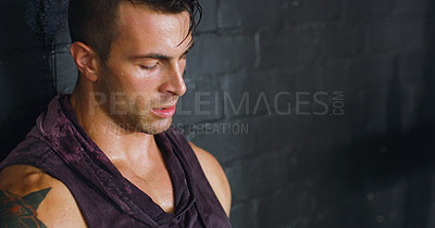 Buy stock photo Shot of a young man looking unhappy after his workout at a gym
