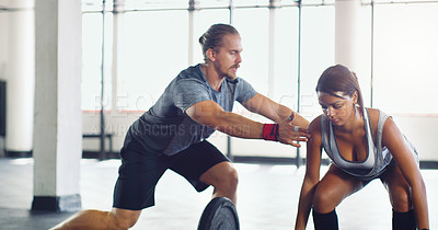 Buy stock photo Shot of a young woman lifting weights with a personal trainer assisting her in a gym