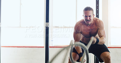 Buy stock photo Shot of a young man working out with battle ropes in a gym