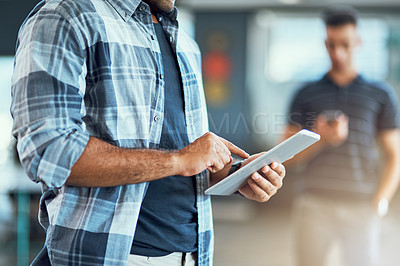 Buy stock photo Closeup shot of an unrecognizable designer using a digital tablet in an office