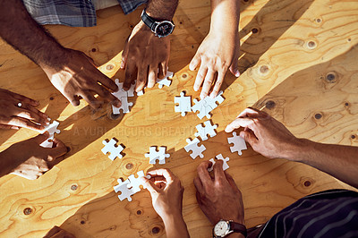 Buy stock photo Closeup shot of an unrecognizable group of people completing a puzzle together