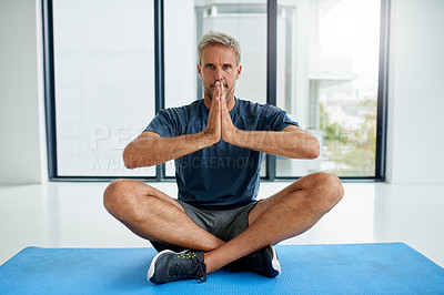 Buy stock photo Portrait of a focused middle aged man seated on a exercise mat on the floor while doing a yoga pose inside of a fitness studio during the day