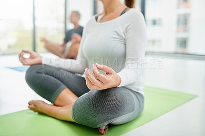 Buy stock photo Shot of an unrecognizable woman seated on a exercise mat with her legs crossed while doing yoga poses inside of a fitness studio