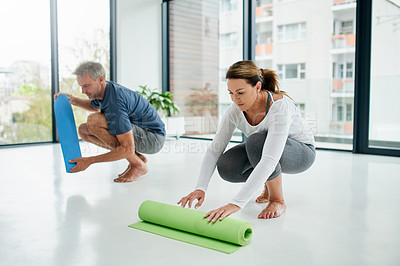 Buy stock photo Shot of a carefree middle aged couple rolling up their exercise mats after a session of doing yoga inside of a fitness studio