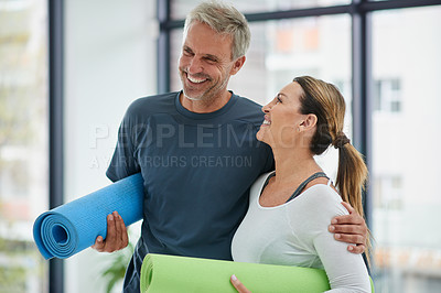 Buy stock photo Shot of a cheerful middle aged couple standing together with their exercise mats after doing yoga inside of a fitness studio