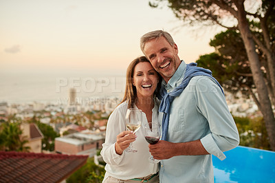 Buy stock photo Portrait of a cheerful middle aged couple holding each other while enjoying a glass of wine outside during the day