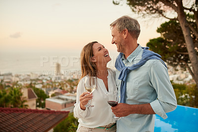 Buy stock photo Shot of a cheerful middle aged couple holding each other while enjoying a glass of wine outside during the day