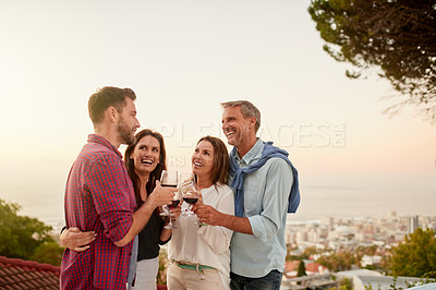 Buy stock photo Shot of a cheerful group of friends enjoying a glass of wine together with the city in the background