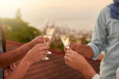 Buy stock photo Shot of a group of unrecognizable people having a celebratory toast with champagne outside during sunset