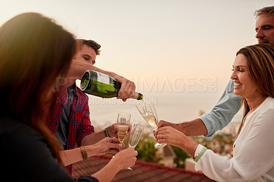 Buy stock photo Shot of a cheerful group of friends enjoying a glass of champagne together with the city in the background