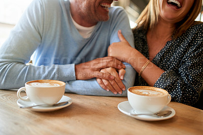 Buy stock photo Cropped shot of a happy mature couple having coffee together at a cafe