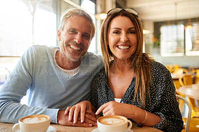 Buy stock photo Shot of a happy mature couple having coffee together at a cafe