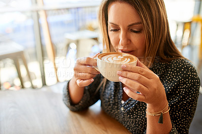Buy stock photo Shot of a mature woman having coffee at a cafe