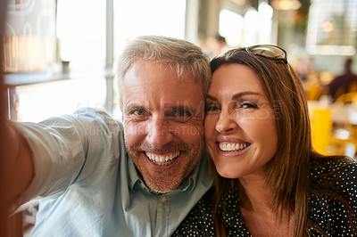 Buy stock photo Shot of a happy mature couple takin a selfie together at a cafe