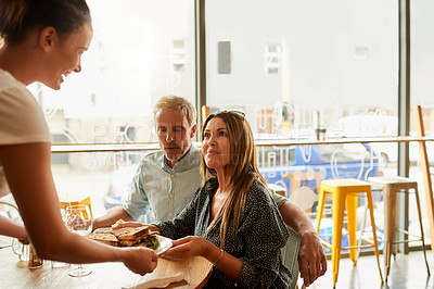 Buy stock photo Shot of a young woman serving a mature couple their meal at a restaurant