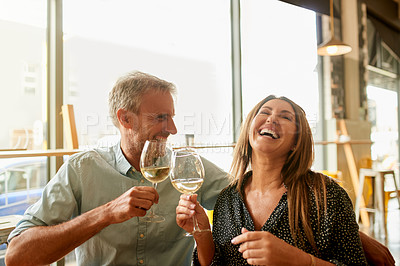Buy stock photo Shot of a mature couple enjoying some wine together at a restaurant