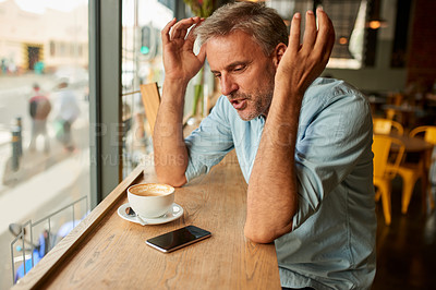 Buy stock photo Shot of a mature man looking stressed out while using his mobile phone at a cafe