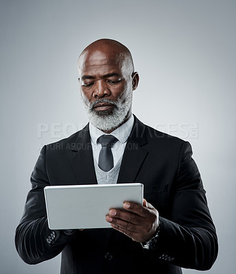Buy stock photo Studio shot of a mature businessman using a digital tablet against a grey background