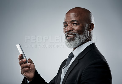 Buy stock photo Studio portrait of a mature businessman using a cellphone against a grey background