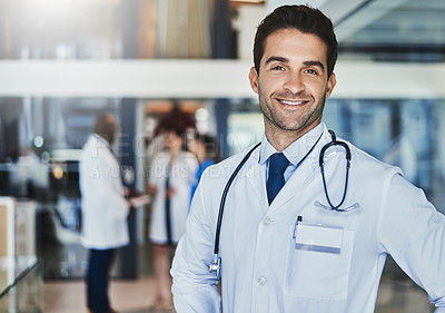 Buy stock photo Portrait of a confident doctor working in a hospital with his colleagues in the background