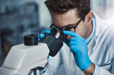 Buy stock photo Cropped shot of a young male scientist working in a lab with a microscope