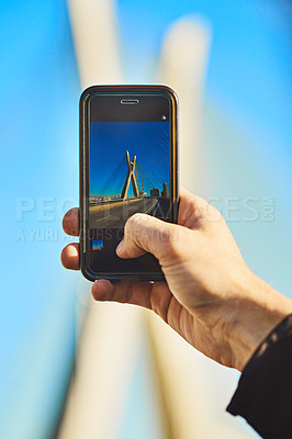 Buy stock photo Cropped shot of an unrecognizable man taking a photo of the city with his cellphone outside