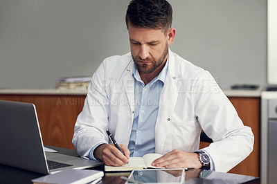Buy stock photo Cropped shot of a handsome male doctor writing in his diary while sitting in his office