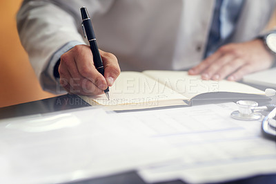 Buy stock photo Cropped shot of an unrecognizable male doctor writing in his diary while sitting in his office