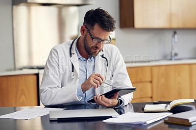 Buy stock photo Cropped shot of a handsome male doctor working on his tablet while sitting in his office