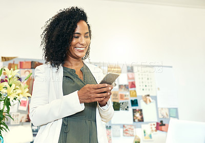Buy stock photo Shot of a designer using her cellphone at the office