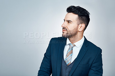 Buy stock photo Studio shot of a handsome young businessman looking thoughtful against a grey background