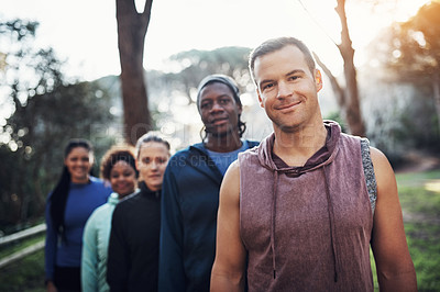 Buy stock photo Portrait of a group of sporty young friends standing in a row while working out in the forest