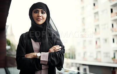 Buy stock photo Cropped portrait of an attractive young businesswoman dressed in Islamic traditional clothing standing with her arms crossed on her office balcony