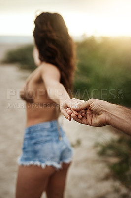 Buy stock photo Shot of a beautiful young woman leading her boyfriend by the hand at the beach