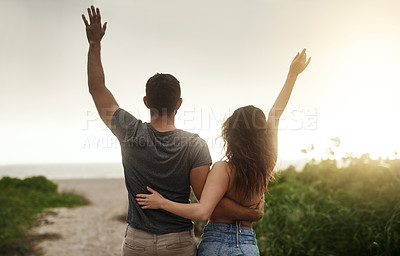 Buy stock photo Rearview shot of a young couple spending a romantic day at the beach