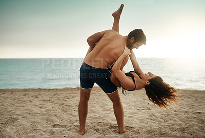Buy stock photo Shot of a young man holding his girlfriend on the beach