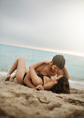Buy stock photo Shot of an affectionate couple laying lovingly on the beach