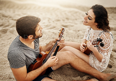 Buy stock photo Shot of a young couple playing ukuleles on the beach