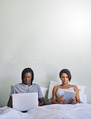 Buy stock photo Shot of a couple sitting in bed while using wireless devices