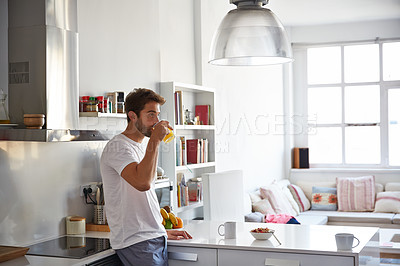 Buy stock photo Shot of a handsome young man drinking juice in the morning at home and looking thoughtful