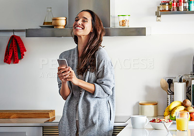 Buy stock photo Shot of a beautiful young woman using a mobile phone in the morning at home