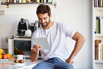 Buy stock photo Shot of a handsome young man using a digital tablet in the morning at home