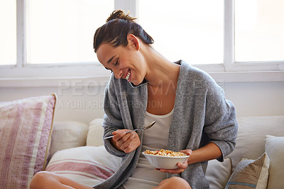 Buy stock photo Shot of a beautiful young woman talking on a mobile phone while having breakfast at home