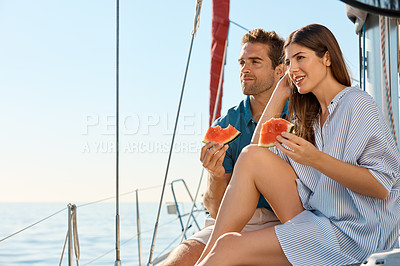 Buy stock photo Shot of a happy young couple eating watermelon on a relaxing ocean cruise