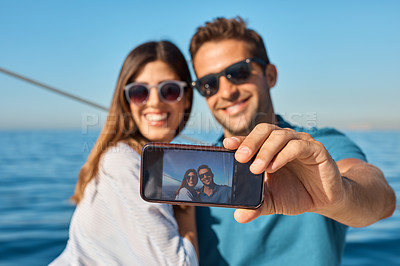 Buy stock photo Shot of a young couple taking a selfie together on an ocean cruise