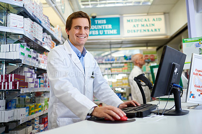 Buy stock photo Portrait of a young pharmacist working on a computer in a chemist