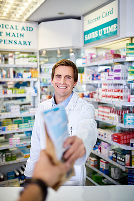 Buy stock photo Personal perspective shot of a pharmacist handing over medication to a customer in a chemist