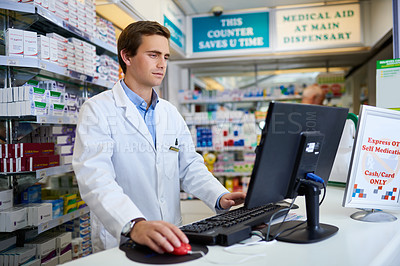 Buy stock photo Shot of a young pharmacist working on a computer in a chemist