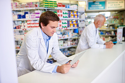 Buy stock photo Shot of a young pharmacist using a digital tablet while in a chemist