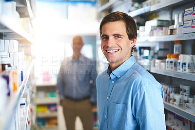 Buy stock photo Cropped portrait of a handsome young man looking for medication in a pharmacy